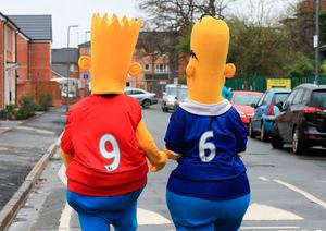 """Fans dressed as Bart and Homer Simpson before the Premier League match at Anfield, Liverpool. PRESS ASSOCIATION Photo. Picture date: Saturday April 1, 2017. See PA story SOCCER Liverpool. Photo credit should read: Peter Byrne/PA Wire. RESTRICTIONS: EDITORIAL USE ONLY No use with unauthorised audio, video, data, fixture lists, club/league logos or """"live"""" services. Online in-match use limited to 75 images, no video emulation. No use in betting, games or single club/league/player publications."""