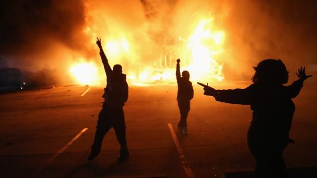 FERGUSON, MO - NOVEMBER 24:  Demonstrators celebrate as a business burns after it was set on fire during rioting following the grand jury announcement in the Michael Brown case on November 24, 2014 in Ferguson, Missouri. Ferguson has been struggling to return to normal after Brown, an 18-year-old black man, was killed by Darren Wilson, a white Ferguson police officer, on August 9. His death has sparked months of sometimes violent protests in Ferguson. A grand jury today declined to indict officer Wilson.  (Photo by Scott Olson/Getty Images)