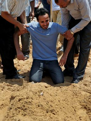 Palestinians try to comfort Hassan al-Halaq, weeping over the graves of his wife Samar, 29, his mother Souad, 62, and his sons Kenan, 5, and Sadji, killed Sunday by an Israeli strike at their house in Gaza City, during their funeral, Monday, July 21, 2014. (AP Photo/Lefteris Pitarakis)