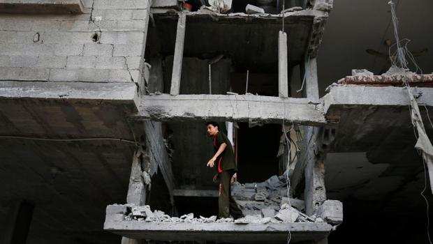 A Palestinian looks at the damage to a house following an overnight Israeli missile strike in Gaza City, Tuesday, July 15, 2014. Egypt presented a cease-fire plan Monday to end a week of heavy fighting between Israel and Hamas militants in the Gaza Strip that has left at least 185 people dead, and both sides said they were seriously considering the proposal. The late-night offer by Egypt marked the first sign of a breakthrough in international efforts to end the conflict. (AP Photo/Lefteris Pitarakis)