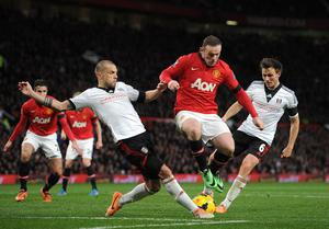 Manchester United's Wayne Rooney (centre) takes on Fulham's William Kvist (right) and Johnny Heitinga during the Barclays Premier League match at Old Trafford, Manchester.