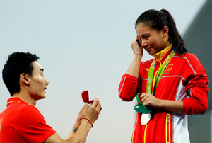 Chinese diver Qin Kai proposes to silver medalist He Zi of China on the podium during the medal ceremony for the Women's Diving 3m Springboard Final on Day 9 of the Rio 2016 Olympic Games at Maria Lenk Aquatics Centre on August 14, 2016 in Rio de Janeiro, Brazil.  (Photo by Clive Rose/Getty Images)