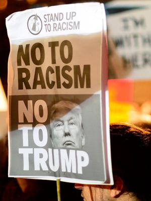 EDINBURGH, SCOTLAND - JANUARY 30: A placard is held aloft as crowds listen to a speaker at the Mound as demonstrators march to the Scottish Parliament to protest against President Trump's Muslim travel ban to the USA on January 30, 2017 in Edinburgh, Scotland. President Trump signed an executive order on Friday banning immigration to the USA from seven muslim countries. This led to protests across America and, today, in the UK a British petition asking for the downgrading of Trump's State visit passed one million signatures this morning. (Photo by Mark Runnacles/Getty Images)