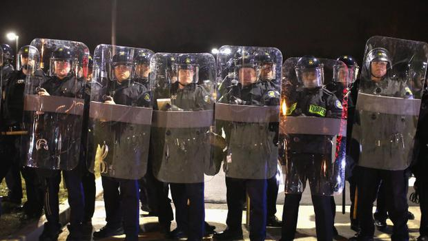 FERGUSON, MO - NOVEMBER 24:  Police guard the Ferguson police department as demonstrators wait for the grand jury announcement in the Michael Brown case on November 24, 2014 in Ferguson, Missouri. Ferguson has been struggling to return to normal after Brown, an 18-year-old black man, was killed by Darren Wilson, a white Ferguson police officer, on August 9. His death has sparked months of sometimes violent protests in Ferguson. A grand jury today declined to indict officer Wilson.  (Photo by Scott Olson/Getty Images)