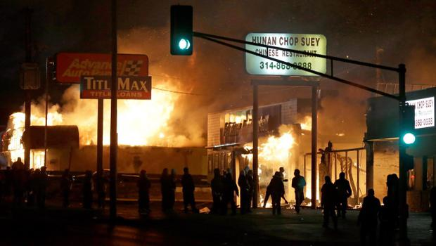 People gather around the burning stores Tuesday, Nov. 25, 2014, in Ferguson, Mo. A grand jury has decided not to indict Ferguson police officer Darren Wilson in the death of Michael Brown, the unarmed, black 18-year-old whose fatal shooting sparked sometimes violent protests. (AP Photo/David Goldman)