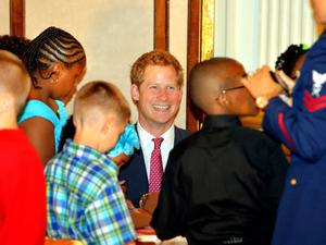 WASHINGTON, DC - MAY 09:  HRH Prince Harry laughs with children who are making presents for their mothers during the first day of his visit to the United States on May 9, 2013 in Washington, DC. HRH will be undertaking engagements on behalf of charities with which the Prince is closely associated on behalf also of HM Government, with a central theme of supporting injured service personnel from the UK and US forces. (Photo by John Stillwell - WPA Pool/Getty Images)