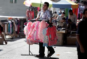 A shop owner carries merchandise outside his shop at a market in Gaza City, northern Gaza Strip, Wednesday, Aug. 6, 2014.  (AP Photo/Lefteris Pitarakis)