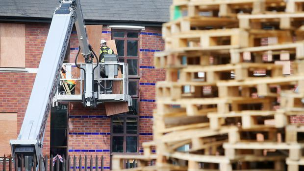 Workmen board up windows of property beside a bonfire at the end of the Comber Greenway off Ravenscroft Avenue in east Belfast. [Photo: Jonathan Porter/PressEye.com]