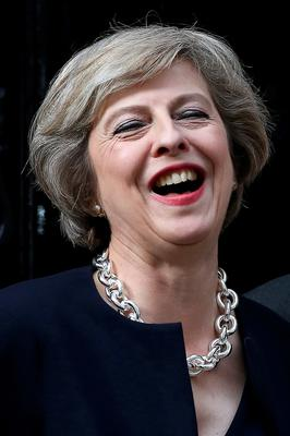 Britain's new Prime Minister Theresa May laughs on the step outside 10 Downing Street in central London on July 13, 2016 on the day she takes office following the formal resignation of David Cameron.  Theresa May took office as Britain's second female prime minister on July 13 charged with guiding the UK out of the European Union after a deeply devisive referendum campaign ended with Britain voting to leave and David Cameron resigning.   / AFP PHOTO / JUSTIN TALLISJUSTIN TALLIS/AFP/Getty Images