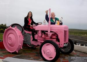 Moyle District Council Chairperson Cara McShane pictured with her father Seamus at the Sheep Island hostel in Ballintoy. Seamus, who has painted his Harry Ferguson tractor pink, says preparations are well underway across the North Coast in preparation for the Giro dItalia cycling race. Picture by Kevin McAuley Photography