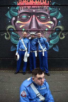 BELFAST, NORTHERN IRELAND - JULY 12:  Supporters of the Orange Order pose by a wall mural during the Twelfth of July parade on July 12, 2019 in Belfast, Northern Ireland. Orangemen march annually on July 12th to commemorate the Protestant King William III's victory over the Catholic King James II at the Battle of the Boyne in 1690. (Photo by Charles McQuillan/Getty Images)