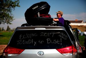 "CASPER, WY - AUGUST 21:  Brian Marriott of Boston, Massachusetts looks in a storage container on top of his car before watching the solar eclipse at South Mike Sedar Park on August 21, 2017 in Casper, Wyoming.  Millions of people have flocked to areas of the U.S. that are in the ""path of totality"" in order to experience a total solar eclipse. During the event, the moon will pass in between the sun and the Earth, appearing to block the sun. (Photo by Justin Sullivan/Getty Images)"