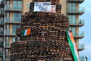 Children atop the huge bonfire in Sandy Row, Belfast with a banner displaying an offensive message directed at SDLP MLA Clare Hanna. PA