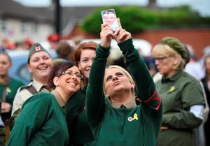 BELFAST, NORTHERN IRELAND - JULY 12: Female band members dressed in military outfits from the first world war take a selfie on a smartphone before they take part in the annual Orange march on July 12, 2016 in Belfast, Northern Ireland. The Orange marches and demonstrations celebrate the Battle of the Boyne in 1690 when the Protestant King William of Orange defeated the Catholic King James II on the banks of the river Boyne. (Photo by Charles McQuillan/Getty Images)