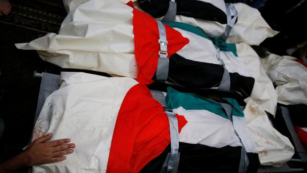 A Palestinian places his hand on one of the five national flag-draped bodies of members of the al-Halaq immediate and extended family, killed Sunday by an Israeli strike at their house in Gaza City, during their funeral at a mosque, Monday, July 21, 2014.  (AP Photo/Lefteris Pitarakis)
