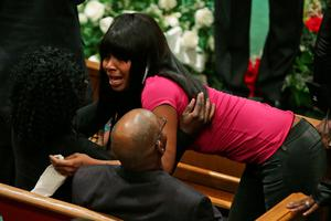 BALTIMORE, MD - APRIL 27:  A mourner cries as she gives their condolences to members of Freddie Gray's family during his funeral at the New Shiloh Baptist Church during his funeral April 27, 2015 in Baltimore, Maryland. Gray, 25, was arrested for possessing a switch blade knife April 12 outside the Gilmor Homes housing project on Baltimore's west side. According to his attorney, Gray died a week later in the hospital from a severe spinal cord injury he received while in police custody.  (Photo by Chip Somodevilla/Getty Images)