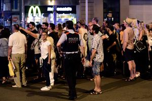 """Tourists wait for the police to allow them to come back to their hotel on the Rambla boulevard after a van ploughed into the crowd, killing at least 13 people and injuring around 100 others is towed away from the Rambla in Barcelona, on August 18, 2017. A driver deliberately rammed a van into a crowd on Barcelona's most popular street on August 17, 2017 killing at least 13 people before fleeing to a nearby bar, police said.  Officers in Spain's second-largest city said the ramming on Las Ramblas was a """"terrorist attack"""". The driver of a van that mowed into a packed street in Barcelona is still on the run, Spanish police said. / AFP PHOTO / JAVIER SORIANOJAVIER SORIANO/AFP/Getty Images"""