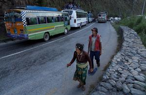 Local residents walk past vehicles held up in a traffic jam on the mountain highway from Kathmandu near the epicenter of Saturday's massive earthquake in the Gorkha District, Nepal, Monday, April 27, 2015. Shelter, fuel, food, medicine, power, news, workers  Nepal's earthquake-hit capital was short on everything Monday as its people searched for lost loved ones, sorted through rubble for their belongings and struggled to provide for their families' needs. (AP Photo/Wally Santana)