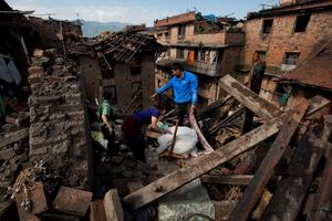 A Nepalese family collects belongings from their home destroyed in Saturday's earthquake, in Bhaktapur on the outskirts of Kathmandu, Nepal, Monday, April 27, 2015. A strong magnitude earthquake shook Nepals capital and the densely populated Kathmandu valley on Saturday devastating the region and leaving tens of thousands shell-shocked and sleeping in streets. (AP Photo/Niranjan Shrestha)