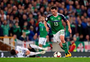 Northern Ireland's Corry Evans brings the ball away after challenging Germany's Sebastian Rudy (floor) for the ball during the 2018 FIFA World Cup Qualifying, Group C match at Windsor Park, Belfast. PRESS ASSOCIATION Photo. Picture date: Thursday October 5, 2017. See PA story SOCCER N Ireland. Niall Carson/PA Wire.