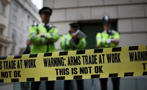 LONDON, ENGLAND - JUNE 12:  Police stand behind some anti-arms trade cordon tape during protests outside arms manufacturer BAe Systems on June 12, 2013 in London, England. Protests are expected to take place in London in the lead up to the G8 meeting to be held in Enniskillen, Northern Ireland on the 17 and 18 June 2013. The chosen location is only 8 kilometers from the scene of one of Northern Ireland's worst killings back in 1987, however Cameron is confident that it's secluded location will deter any potential trouble.  (Photo by Peter Macdiarmid/Getty Images)