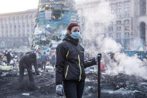 KIEV, UKRAINE - FEBRUARY 20: A woman clears ashes and debris with other anti-government protesters from a newly-occupied portion of Independence Square on February 20, 2014 in Kiev, Ukraine. Dozens of protesters were reportedly been killed after violence flared again between police and anti-government protesters, who are calling to oust President Viktor Yanukovych over corruption and an abandoned trade agreement with the European Union.  (Photo by Brendan Hoffman/Getty Images)