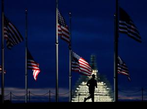 WASHINGTON, DC - SEPTEMBER 11:  A man jogs past a row of American flags that have been lowered to half staff on the Washington Monument grounds, near the US Capitol on September 11, 2015 in Washington, DC. Today marks the fourteenth anniversary of the September 11, 2001 attacks when terroristists high jacked airliners and flew them in the World Trade Center and the Pentagon.  (Photo by Mark Wilson/Getty Images)