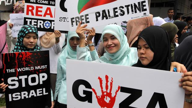 Thai-Muslim activists hold up banners during a rally outside the Israeli embassy in Bangkok, Thailand Tuesday, July 15, 2014. Several hundreds of activists took part in the rally to show solidarity for Palestine against Israel's attacks on Gaza. (AP Photo/Apichart Weerawong)