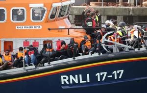 A group of people thought to be migrants are brought into Dover, Kent, by the RNLI on Wednesday