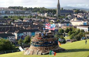 Flags to be burnt on top of a bonfire, in the bogside area of Londonderry, which is traditionally torched on August 15 to mark a Catholic feast day celebrating the assumption of the Virgin Mary into heaven, but in modern times the fire has become a source of contention and associated with anti-social behaviour. PRESS ASSOCIATION Photo. Picture date: Tuesday August 15, 2017. Disorder flared in Londonderry on Monday night as bonfire-builders attacked police and members of the public. Police said those gathered at the controversial fire site in Derry's Bogside threw rocks and stones at local people before targeting police with petrol bombs and other missiles. See PA story ULSTER Bonfire. Photo credit should read: Niall Carson/PA Wire
