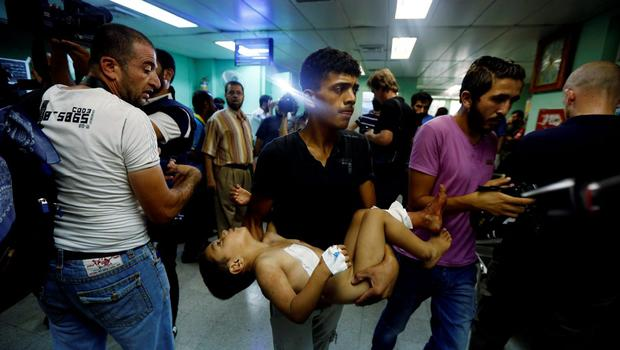 A Palestinian man carries a child, wounded in an Israeli strike on a compound housing a UN school in Beit Hanoun, in the northern Gaza Strip, cries at the emergency room of the Kamal Adwan hospital in Beit Lahiya, Thursday, July 24, 2014. (AP Photo/Lefteris Pitarakis)