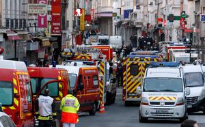 Police and Ambulance vans are parked in Saint-Denis, a northern suburb of Paris, Wednesday, Nov. 18, 2015. Police say two suspects in last week's Paris attacks, a man and a woman, have been killed in a police operation north of the capital. Two police officers have been injured in the standoff. Police have said the operation is targeting the suspected mastermind of last week's attacks, believed to be holed up in an apartment in Saint-Denis with several other heavily armed suspects. (AP Photo/Francois Mori)