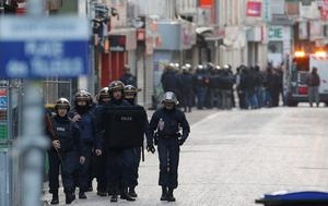 Special police forces walk through Saint-Denis, a northern suburb of Paris, Wednesday, Nov. 18, 2015. Police say two suspects in last week's Paris attacks, a man and a woman, have been killed in a police operation north of the capital. Two police officers have been injured in the standoff. Police have said the operation is targeting the suspected mastermind of last week's attacks, believed to be holed up in an apartment in Saint-Denis with several other heavily armed suspects. (AP Photo/Chistophe Ena)