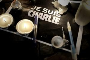 """A candle is lit near a paper with the written words """"I am Charlie"""" in french at a vigil in front of the French Embassy following the terrorist attack in Paris on January 7, 2015 in Berlin, Germany. Twelve people were killed including two police officers as two gunmen opened fire at the offices of the French satirical publication Charlie Hebdo.  (Photo by Carsten Koall/Getty Images)"""