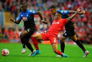LIVERPOOL, ENGLAND - AUGUST 17:  (L-R) Joshua King (R) and Max Gradel of Bournemouth (L) battle with Nathaniel Clyne of Liverpool (C) during the Barclays Premier League match between Liverpool and A.F.C. Bournemouth at Anfield on August 17, 2015 in Liverpool, United Kingdom.  (Photo by Alex Livesey/Getty Images)
