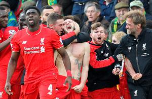 With his shirt off, Liverpool's English midfielder Adam Lallana (C) celebrates scoring their late winning goal with teammates and Liverpool's German manager Jurgen Klopp (3rd R), as Norwich City's Scottish coach Alex Neil (R) looks on during the English Premier League football match between Norwich City and Liverpool at Carrow Road in Norwich, eastern England, on January 23, 2016. Liverpool won the game 5-4. AFP/Getty Images