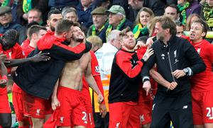 With his shirt off, Liverpool's English midfielder Adam Lallana (C) celebrates scoring their late winning goal with teammates and Liverpool's German manager Jurgen Klopp (2nd R) during the English Premier League football match between Norwich City and Liverpool at Carrow Road in Norwich, eastern England, on January 23, 2016. Liverpool won the game 5-4. AFP PHOTO / LINDSEY PARNABY  RESTRICTED TO EDITORIAL USE. No use with unauthorized audio, video, data, fixture lists, club/league logos or 'live' services. Online in-match use limited to 75 images, no video emulation. No use in betting, games or single club/league/player publications.LINDSEY PARNABY/AFP/Getty Images