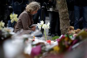 A woman spends a moment mourning the dead at the site of the attack at the Cafe Belle Equipe on rue de Charonne in the 11th district, prior to going to work early on November 16, 2015 in Paris, three days after the terrorist attacks that left over 130 dead and more than 350 injured. France prepared to fall silent at noon on November 16 to mourn victims of the Paris attacks after its warplanes pounded the Syrian stronghold of Islamic State, the jihadist group that has claimed responsibility for the slaughter.  AFP PHOTO / KENZO TRIBOUILLARDKENZO TRIBOUILLARD/AFP/Getty Images