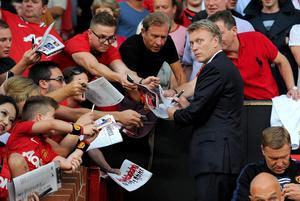 Manchester United manager David Moyes signs autographs for fans prior to kick-off during the Barclays Premier League match at Old Trafford, Manchester. PRESS ASSOCIATION Photo. Picture date: Monday August 26, 2013. See PA story SOCCER Man Utd. Photo credit should read: Martin Rickett/PA Wire. RESTRICTIONS: Editorial use only. Maximum 45 images during a match. No video emulation or promotion as 'live'. No use in games, competitions, merchandise, betting or single club/player services. No use with unofficial audio, video, data, fixtures or club/league logos.