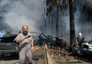 A Lebanese man takes pictures with his mobile phone at the site of an explosion outside a mosque in the Northern city of Tripoli, Lebanon, Friday Aug. 23, 2013.  Lebanon's official news agency says dozens of people have been killed by twin explosions outside two Sunni mosques in a northern city. The explosions in Tripoli come amid rising tensions in Lebanon resulting from Syria's civil war, which has sharply polarized the country along sectarian lines and between supporters and opponents of the regime of President Bashar Assad. Tripoli has previously seen clashes between Sunnis and Alawites, a Shiite offshoot sect to which Assad belongs.(AP Photo)