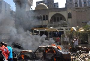 A burning car is seen at the entrance of a mosque which was attacked by a car bomb, in the northern city of Tripoli, Lebanon, Friday, Aug. 23, 2013. Lebanon's official news agency says dozens of people have been killed by twin explosions outside two Sunni mosques in a northern city. The explosions in Tripoli come amid rising tensions in Lebanon resulting from Syria's civil war, which has sharply polarized the country along sectarian lines and between supporters and opponents of the regime of President Bashar Assad. Tripoli has previously seen clashes between Sunnis and Alawites, a Shiite offshoot sect to which Assad belongs.(AP Photo)