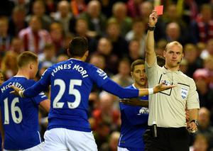Referee Bobby Madley (R) shows Everton's Argentinian defender Ramiro Funes Mori a red card during the English Premier League football match between Liverpool and Everton at Anfield in Liverpool, north west England on April 20, 2016. / AFP PHOTO / PAUL ELLIS / RESTRICTED TO EDITORIAL USE. No use with unauthorized audio, video, data, fixture lists, club/league logos or 'live' services. Online in-match use limited to 75 images, no video emulation. No use in betting, games or single club/league/player publications.  / PAUL ELLIS/AFP/Getty Images