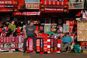 MANCHESTER, ENGLAND - APRIL 01:  A street vendor sells merchandise ahead of the UEFA Champions League Quarter Final first leg match between Manchester United and FC Bayern Muenchen at Old Trafford on April 1, 2014 in Manchester, England.  (Photo by Michael Regan/Bongarts/Getty Images)