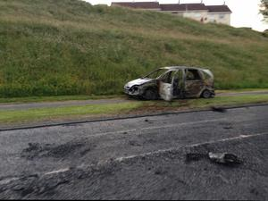 A burnt car sits on the O'Neill Road in the Carnmoney Area