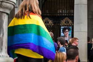 A woman with a rainbow flag at a vigil at Belfast City Hall in memory of murdered journalist Lyra McKee. PRESS ASSOCIATION Photo. Picture date: Friday April 19, 2019. See PA story ULSTER Unrest Vigil. Photo credit should read: Liam McBurney/PA Wire