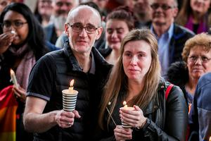 People hold candles during a vigil at Belfast City Hall in memory of murdered journalist Lyra McKee. PRESS ASSOCIATION Photo. Picture date: Friday April 19, 2019. See PA story ULSTER Unrest Vigil. Photo credit should read: Liam McBurney/PA Wire