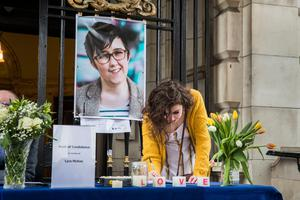 People signing a book of condolence after a vigil at Belfast City Hall in memory of murdered journalist Lyra McKee. PRESS ASSOCIATION Photo. Picture date: Friday April 19, 2019. See PA story ULSTER Unrest Vigil. Photo credit should read: Liam McBurney/PA Wire