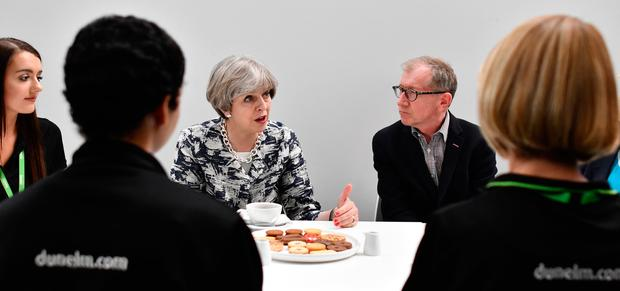 Britain's Prime Minister and leader of the Conservative Party Theresa May and husband Philip speak to staff at a Dunelm department store during a campaign visit on June 7, 2017 in Nottingham, England.  Britain goes to the polls tomorrow June 8 to vote in a general election.  (Photo by Ben Stansall - WPA Pool/Getty Images)