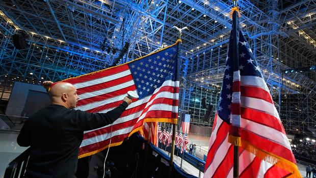 A worker sreams a US flag at the Jacob K. Javits Convention Center in New York on November 8, 2016 where Democratic presidential candidate Hillary Clinton's election night event is held. Eager voters crowded into polling stations to choose a new US president Tuesday after a wild and bitter contest between the billionaire populist Donald Trump and Hillary Clinton, the Democrat seeking to become the first woman to win the White House. / AFP PHOTO / Angela WEISSANGELA WEISS/AFP/Getty Images