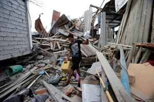 """A man, whose wife and unborn son were killed during a 7.8-magnitude earthquake, recovers belongings from his collapsed home, in La Chorrera, Ecuador, Monday, April 18, 2016. The Saturday night quake left a trail of ruin along Ecuador's normally placid Pacific Ocean coast. At least 350 people died and thousands are homeless. President Rafael Correa said early Monday that the death toll would """"surely rise, and in a considerable way."""" (AP Photo/Dolores Ochoa)"""